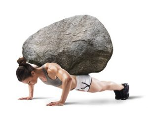 Muscular woman lifts a boulder with back